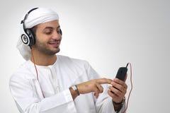 Arabian guy listening to music using headphones isolated