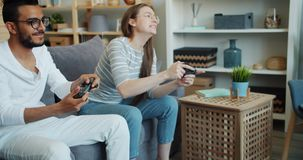 Arabian guy playing video game with cute girlfriend indoors at home. Slow motion of Arabian guy playing video game with cute girlfriend indoors at home having stock video footage