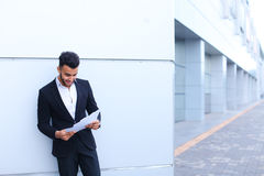 Arabian handsome student smiling, holds and looks at documents n Royalty Free Stock Image