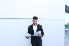 Arabian handsome student smiling, holds and looks at documents n Stock Image