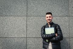 Arabian hipster student standing by stone wall outside. Young smiling man waiting for groupmates stock photography