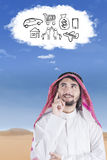 Arabian imagines his dream. Portrait of an arabian man stands and imagines about his dream while wearing islamic clothes stock photo