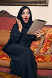 Arabian lady with hijab shocked while using a Pad Royalty Free Stock Image