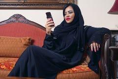 Arabian lady wearing hijab chatting. Using mobile phone stock photos
