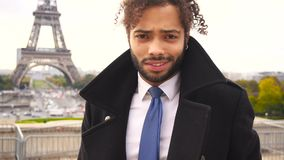 Mulatto male model smiling near Eiffel Tower in slow motion. Arabian lovely guy standing around Eiffel Tower for photo session in slow motion. Young man near stock video