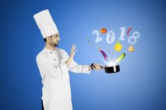 Arabian magician chef with number 2018. Arabian magician chef holding a pan while cooking all food ingredients with smoke shaped number 2018 Stock Photography