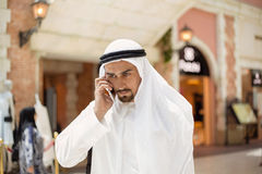 Arabian Male Using Smart Phone. Handsome Arabian Male Using Smart Phone Outdoors. Focus Is On Smart Phone Royalty Free Stock Photos