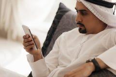 Arabian Male Using Smart Phone Indoors. Handsome Arabian Male Sitting On Sofa And Using Smart Phone Royalty Free Stock Photo