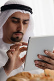 Arabian Male Using Tablet During Breakfast Royalty Free Stock Photo
