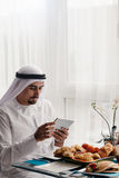 Arabian Male Using Tablet During Breakfast. Handsome Arabian Male Using Digital Tablet During Breakfast Stock Photography