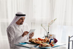 Arabian Male Using Tablet During Breakfast. Handsome Arabian Male Using Digital Tablet During Breakfast Royalty Free Stock Photos