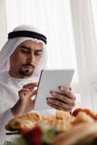 Arabian Male Using Tablet During Breakfast. Handsome Arabian Male Using Digital Tablet During Breakfast Royalty Free Stock Image