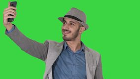 Arabian man in the casual clothes walking and making selfie on a Green Screen, Chroma Key. stock video footage