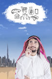 Arabian man looking bubble cloud speech. Arabian man with muslim clothes imagines his dream while looking at bubble cloud speech Royalty Free Stock Images