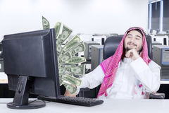 Arabian man looking at money on computer. Portrait arabian man sitting on the chair while looking at money flying out of computer Royalty Free Stock Images