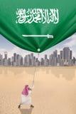 Arabian man pulls flag of Saudi Arabia Royalty Free Stock Photos