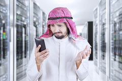 Arabian man reads message in server room. Middle eastern businessman reading message on his smartphone and looks disappointed, shot in the server room Royalty Free Stock Image