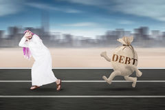 Arabian man running away from debt. Picture of Arabian businessman running away from a money bag with debt word on the road Stock Photos