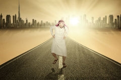 Arabian man running on the road. Picture of funny Arabian businessman smiling at the camera while running on the road, shot outdoors Stock Photography