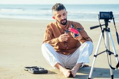 Arabian man sitting on sand and talking tripod video making review of quadrocopter in beach. Travel videographer