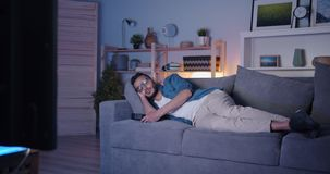 Arabian man sleeping on couch in front of TV relaxing at night in dark flat. Arabian man wearing casual clothing is sleeping on couch in front of tv relaxing at stock video footage