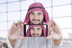 Arabian man smiling at the camera phone. Arabian man wearing turban taking self portrait and smiling at the camera phone in office Royalty Free Stock Images