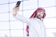 Arabian man taking picture of himself. Arabian businessman wearing turban using mobile phone to take picture of himself in office Royalty Free Stock Photo