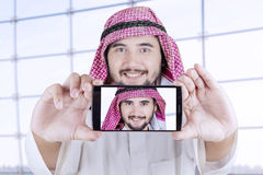 Arabian man taking selfie in airport. Portrait of Arabian person using a mobile phone to take selfie photo in the airport Stock Photo