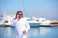 Arabian man talking on the cell phone at the yacht harbor Stock Image