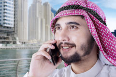 Arabian man talking on cellphone at a town Stock Photos