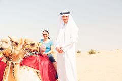 Arabian Man And Tourist Riding A Camel Stock Images