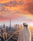 Arabian man watching cityscape of Dubai with modern futuristic architecture in United Arab Emirates. Arabian man watching cityscape of famous Dubai with modern stock images