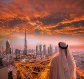 Arabian man watching cityscape of Dubai with modern futuristic architecture in United Arab Emirates. Stock Photo