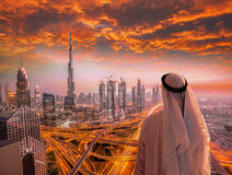 Arabian man watching cityscape of Dubai with modern futuristic architecture in United Arab Emirates. Stock Images
