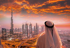 Arabian man watching cityscape of Dubai with modern futuristic architecture in United Arab Emirates. Stock Image