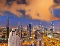 Arabian man watching night cityscape of Dubai with modern futuristic architecture in United Arab Emirates. Arabian man watching night cityscape of famous Dubai stock image