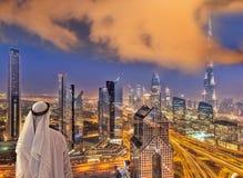 Arabian man watching night cityscape of Dubai with modern futuristic architecture in United Arab Emirates. Arabian man watching night cityscape of famous Dubai royalty free stock image