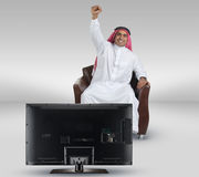 Arabian man watching TV and reacting Royalty Free Stock Image