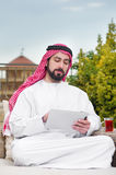 Arabian man working on a mobile tablet & drinking tea Stock Images