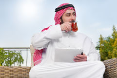Arabian man working on a mobile tablet & drinking tea Royalty Free Stock Photo