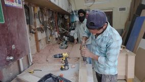 Arabian man works with electric drill at woodworking shop. DUBAI UNITED ARAB EMIRATES - DECEMBER 18 2018: Handsome Arabian man works with electric drill in stock video