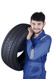 Arabian mechanic lifting car tyre. Portrait of arabian mechanic lifting a car tyre while smiling at the camera, isolated on white background Stock Photography