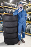 Arabian mechanic with megaphone in workshop. Male mechanic wearing uniform in the workshop and standing next to a pile of tires while holding a megaphone Stock Photo
