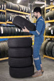 Arabian mechanic pile up tires in workshop. Picture of middle eastern mechanic pile up tires while wearing uniform in the workshop Royalty Free Stock Images