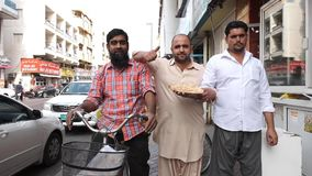 Arabian men stand by food shop in old Dubai street. DUBAI UNITED ARAB EMIRATES - DECEMBER 18 2018: Handsome Arabian men stand by street fast food shop and praise stock video