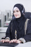 Arabian operator working in the office. Portrait of a female Arabian operator wearing headphone and working in the office Royalty Free Stock Images