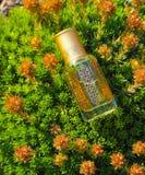 Arabian oud attar perfume or agarwood oil fragrances in mini bottle. Arabian oud attar perfume or agarwood oil fragrances in mini bottles on a natural Stock Image
