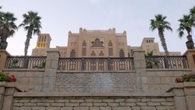 Arabian palace with authentic stone fence in twilight with palm garden and flowerbeds. Tilt up shot stock footage