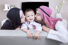 Arabian parents kiss their son at home. Two young Arabian parents kissing their son while sitting on the sofa in the living room Royalty Free Stock Image
