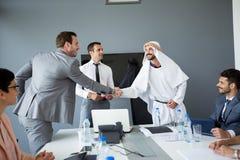 Arabian partner handshake with businessman stock images
